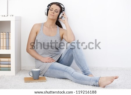 Woman listening to music on headphones with eyes closed, sitting on floor daydreaming.
