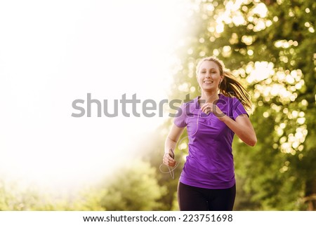 Woman listening to music on her earplugs and MP3 player while jogging along a country road in a healthy lifestyle, exercise and fitness concept - stock photo