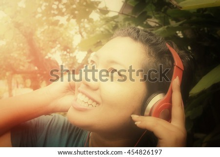 Woman listening to music on red headphones