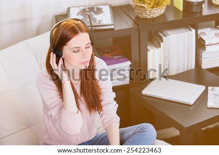 Woman listening to music on the laptop in the room.