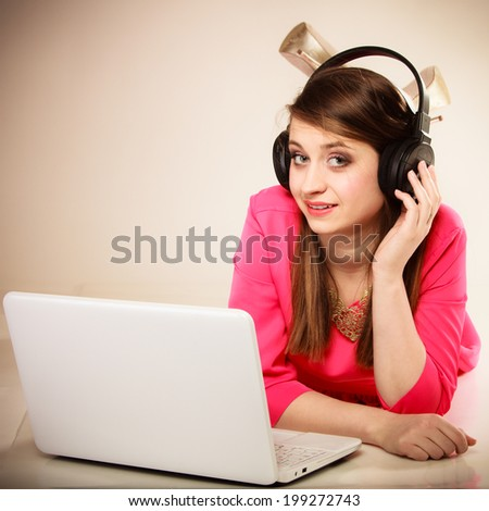Woman listening to music with headphones and using computer laptop. Student girl learning language with new technology.