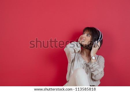 Woman listening to music with headphones next to a red wall