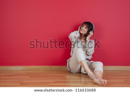 Woman listening to music with headphones sited on the floor at home - stock photo