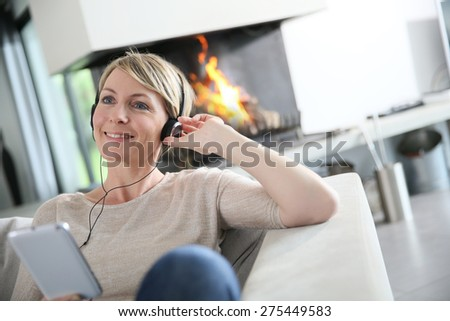 Woman listening to music with smartphone by fireplace