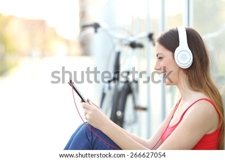 Woman listening to the music from a tablet sitting on the floor in a park with a bicycle in the background - stock photo