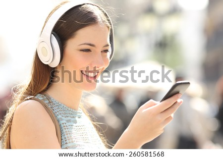 Woman listening wireless music with headphones from a smart phone in the street - stock photo