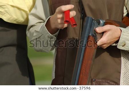 woman loading a shotgun - stock photo