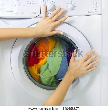 woman loading clothes in the washing machine - stock photo