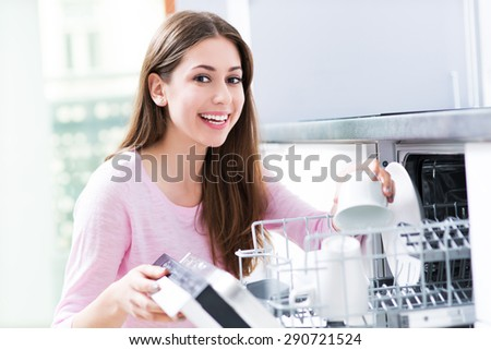 Woman loading dishwasher  - stock photo
