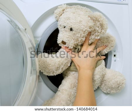 woman loading fluffy toy in the washing machine - stock photo