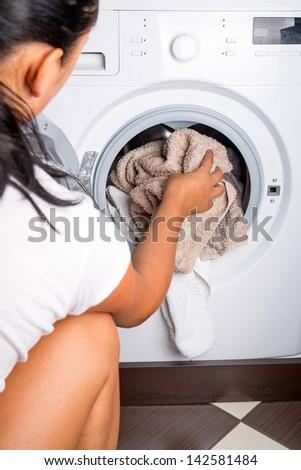 Woman loading laundry to the washing machine - stock photo