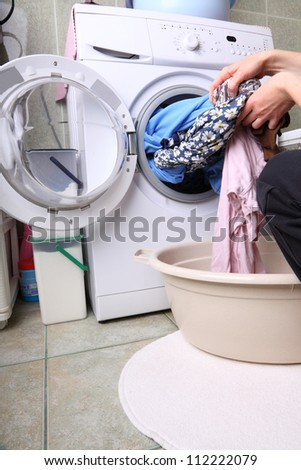 woman loading Preparation washing machine in bathroom clothes in the washing machine