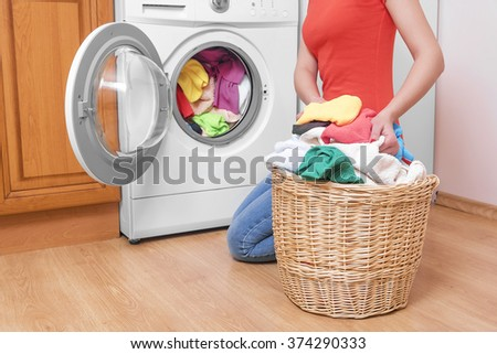 Woman loading the washing machine colored clothing.