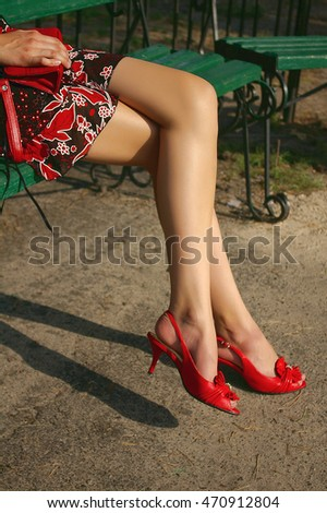 Woman long legs in red high heel shoes, summer dress and fashion red bag sit on bench, outdoor shot/Pair of erotic young woman's legs in red fashion shoes.Sexy girl in a red dress
