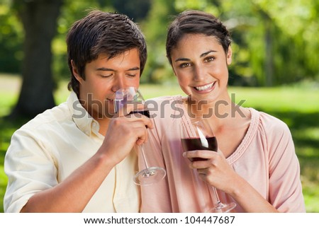 Woman looking ahead and smiling while her friend drinks from a glass of red wine in a park
