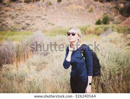 Woman Looking Around While Hiking in High Desert - stock photo