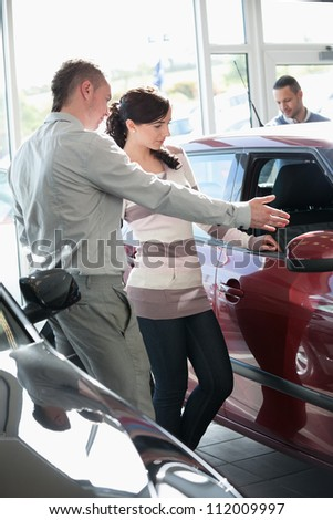 Woman looking at a car interior being pointed by a salesman