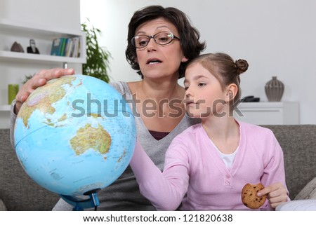 Woman looking at a globe with her granddaughter - stock photo