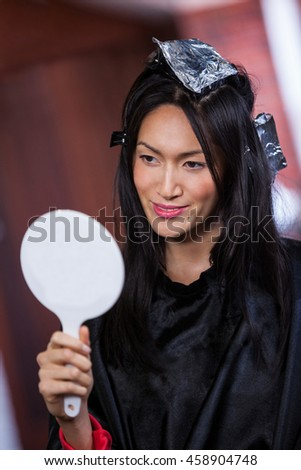Woman looking at a mirror while waiting with hair dye in her head at a salon