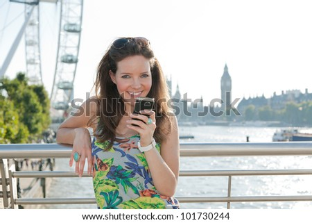 Woman looking at camera smiling, texting from bridge over River Thames, London with attractions in background - stock photo