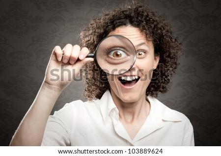 woman looking at camera through magnifying glass - stock photo