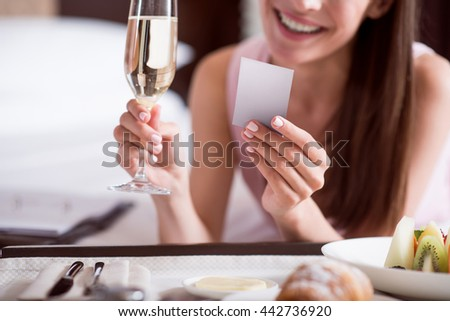 Woman looking at card and holding champagne - stock photo