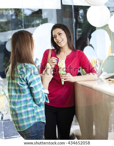 Woman Looking At Daughter While Holding Vanilla Ice Cream Cone - stock photo