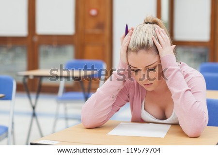 Woman looking at exam paper anxiously in exam hall - stock photo