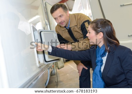 Woman looking at exterior cupboard on motorhome