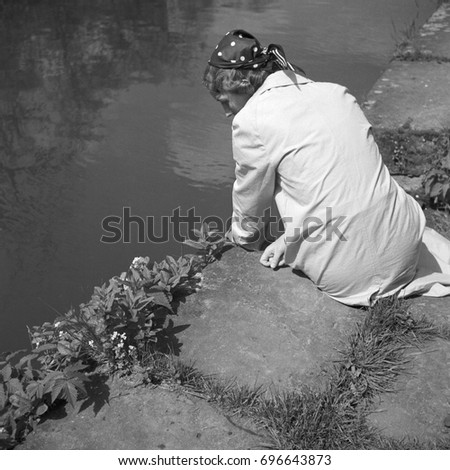 Woman looking at flowers on riverbank