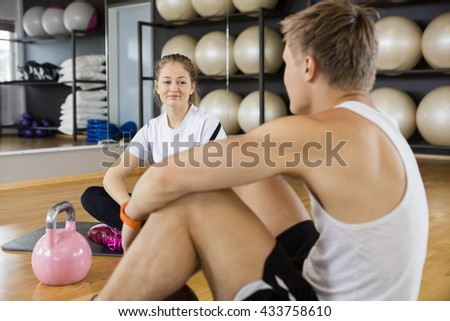 Woman Looking At Friend While Sitting In Gym - stock photo