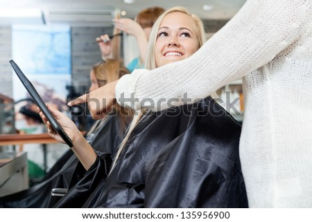 Woman looking at hairdresser while she points on digital tablet's screen - stock photo