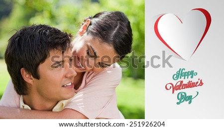 Woman looking at her friend while he is carrying her against cute valentines message - stock photo