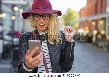 Woman looking at her smartphone in pleasant surprise