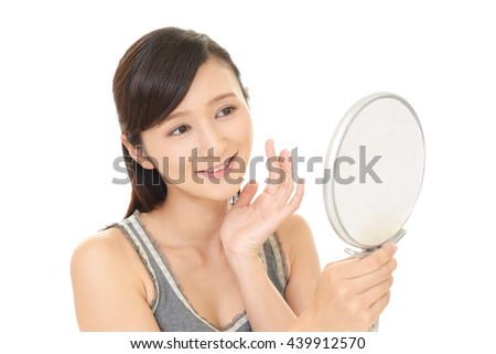 Woman looking at herself in a hand mirror - stock photo