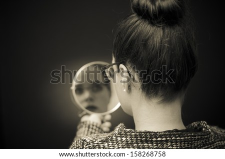 woman looking at herself in mirror - stock photo