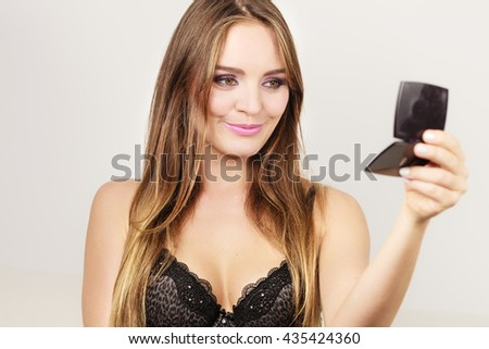 Woman looking at herself in mirror. Attractive pretty gorgeous girl long haired with makeup  - stock photo