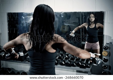 Woman looking at herself in the mirror with barbells in the gym - stock photo