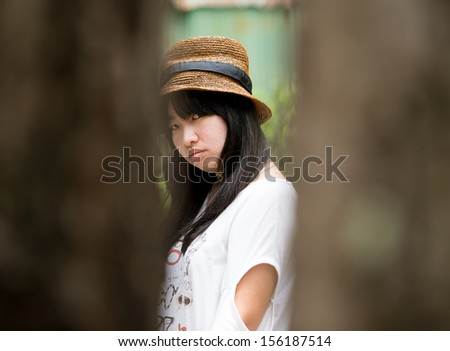 woman looking at hiding camera through fence - stock photo