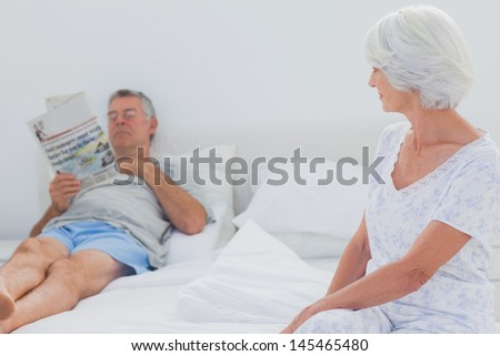 Woman looking at husband reading newspaper in the bed