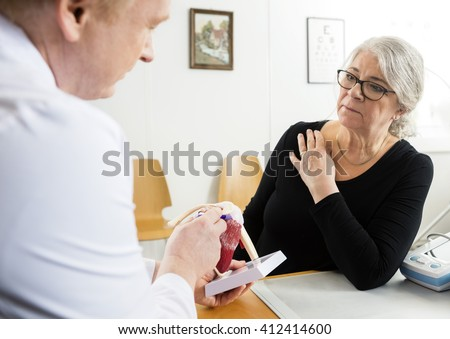 Woman Looking At Male Doctor Explaining Shoulder Rotator Cuff Mo - stock photo