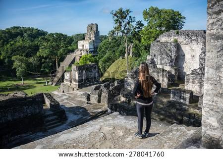 Woman looking at Mayan historic building at Tikal Jungle. Guatemala. - stock photo