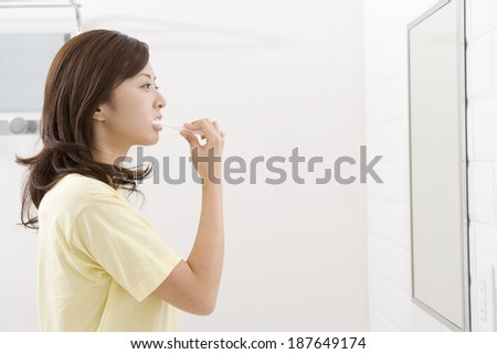 woman looking at mirror brushes her teeth