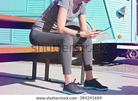 Woman looking at mobile phone after workout. Running, jogging, sport, active lifestyle concept. Female athlete resting and relaxing after workout. - stock photo