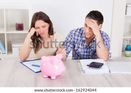 Woman Looking At Piggybank Raised By Young Man - stock photo