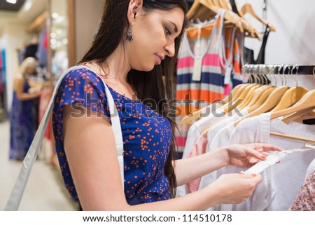 Woman looking at price tag of clothes in shopping mall - stock photo