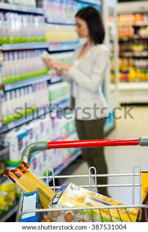 Woman looking at product in aisle in supermarket