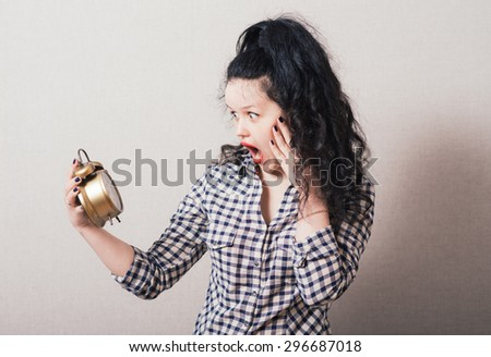 Woman looking at the alarm clock in her hand. On a gray background. - stock photo