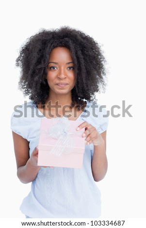 Woman looking at the camera after opening her gift against a white background