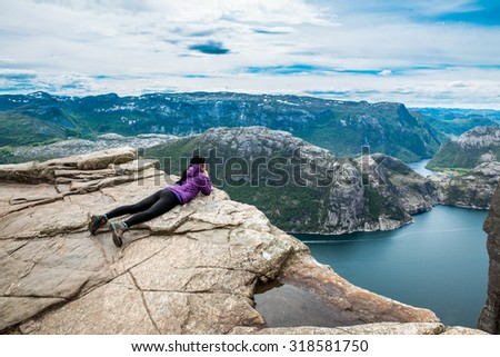 Woman looking at the landscape from a height. Beautiful Nature Norway Preikestolen or Prekestolen. - stock photo